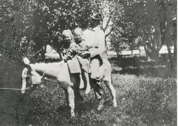 Dr. Chandler on a burro with his neices Louise and Marian.jpg